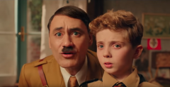 "A frame from the movie ""Jojo Rabbit"" – a 10uo boy stands next to his imaginary friend, Hitler"