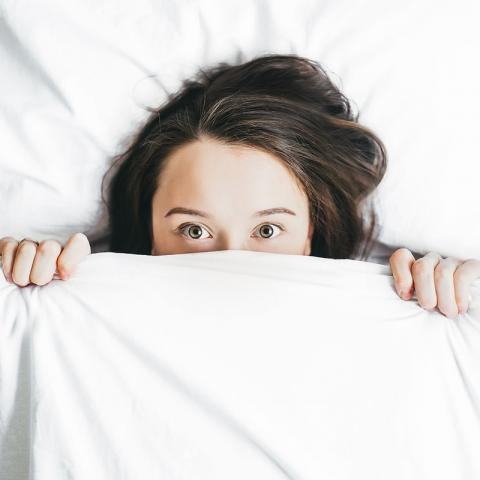 Woman covering her face under a bedsheet
